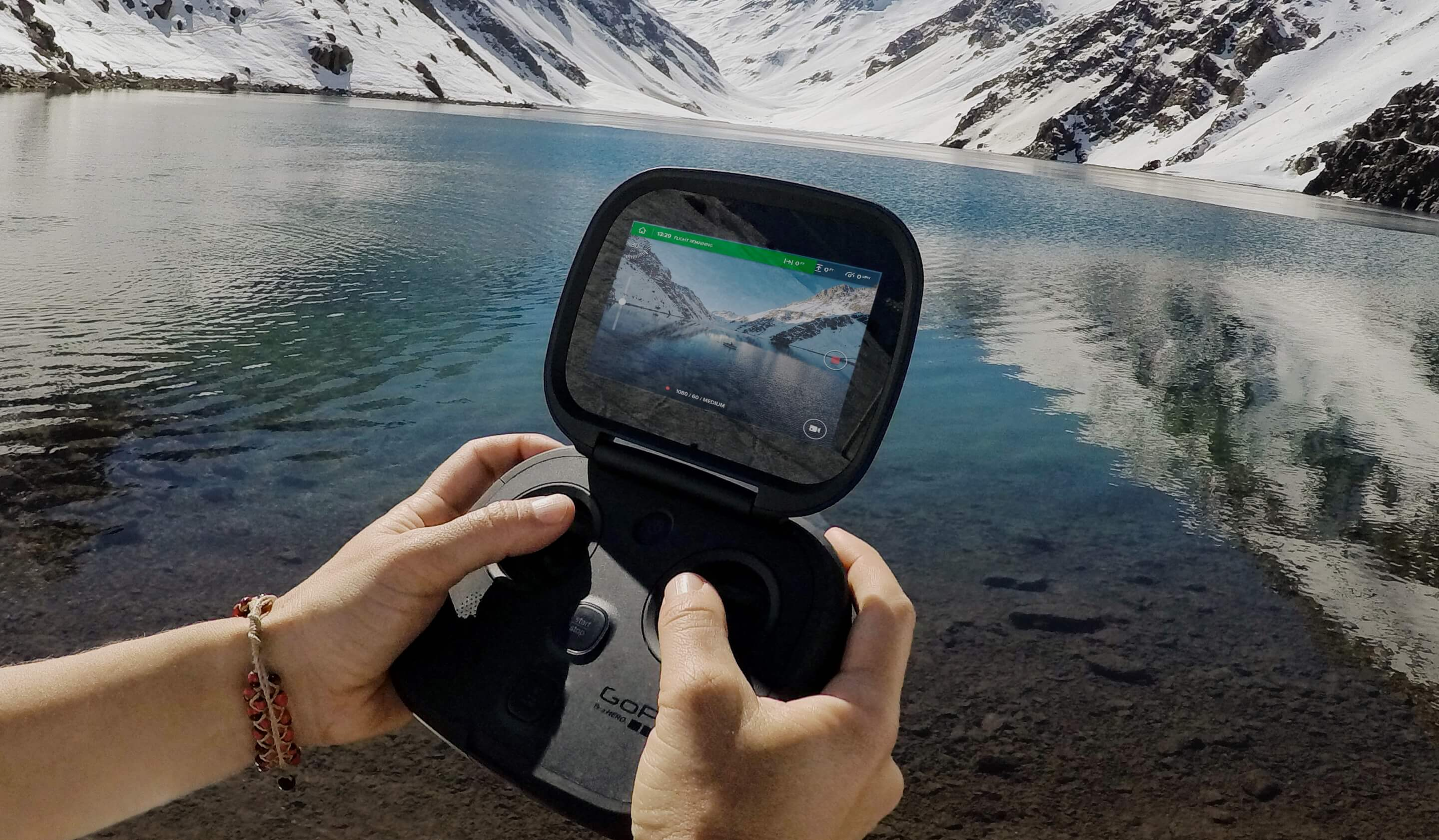 user holding gopro karma controller with water and snowy mountains in the background