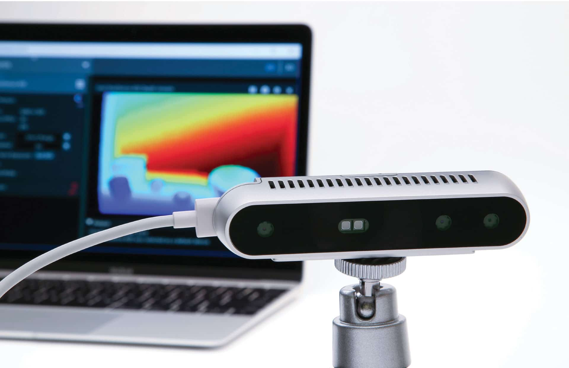 photo of intel realsense camera on a tripod plugged in with a laptop in the background